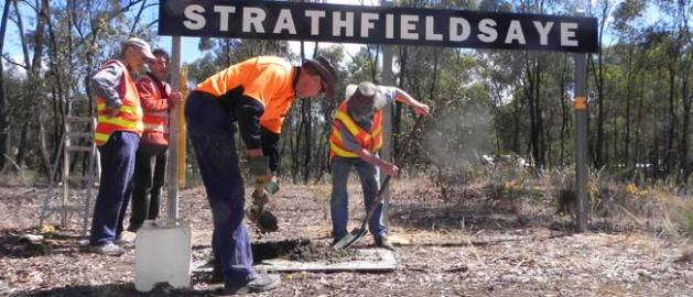 Four men wearing orange safety vests installing the Strathfieldsaye station sign