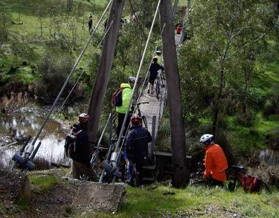 Cyclists crossing the suspension bridge at Axe Creek