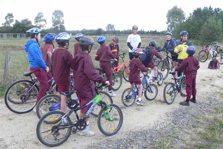 Primary students on bikes prepare to ride to school along the trail