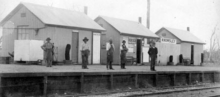 Five men standing on Knowsley railway station platform