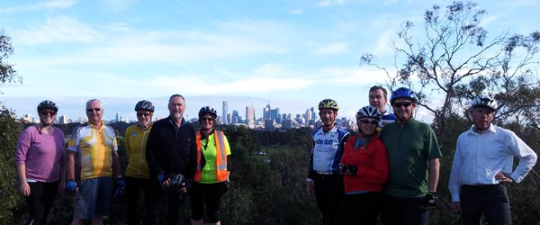 Ten people lined up on hill top with Melbourne city skyline in background