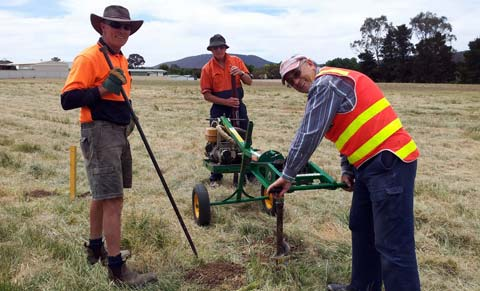 Three men in a paddock with a post-hole borer and a shovel.