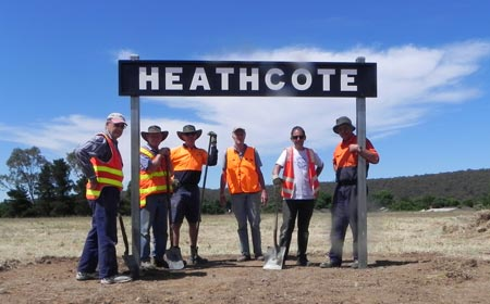 Six men in orange safety vests lined up underneath Heathcote station sign