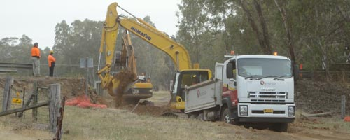 Digging machinery breaks a hole right through the highway