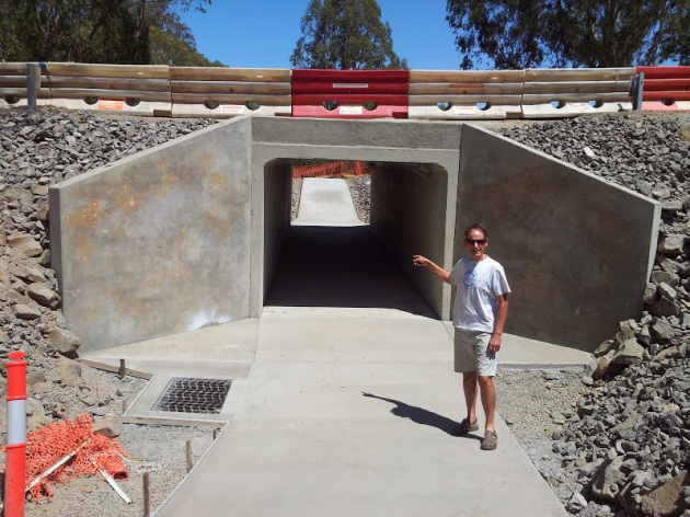 Man standing on concrete ramp leading to tunnel under a road