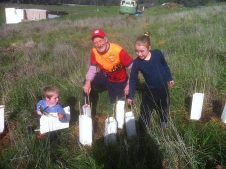 Friends of Bendigo-Kilmore Rail Trail member Mal Ward and grandchildren planting trees. 31 July 2016